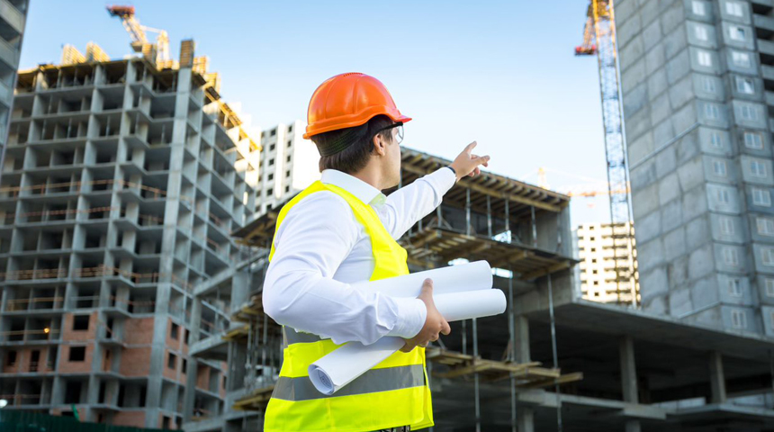 engineer pointing to the ongoing construction of buildings